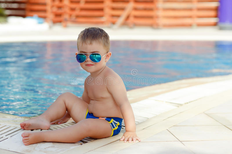 Small charming chubby baby boy in glasses sitting on a pool back stock photos
