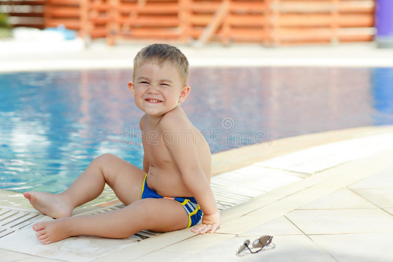 Small charming chubby baby boy sitting on a background of the po stock images