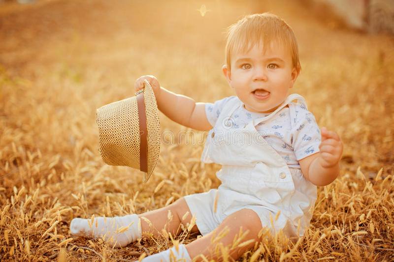 Small charming chubby little boy in a white suit holding a hat , stock image