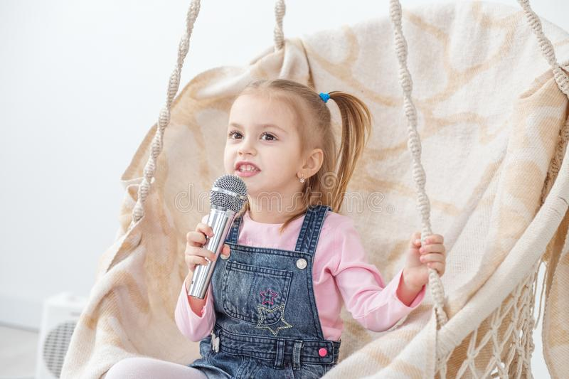 A small cheerful child learns to sing songs. The concept of childhood, performer, life style, music. royalty free stock images