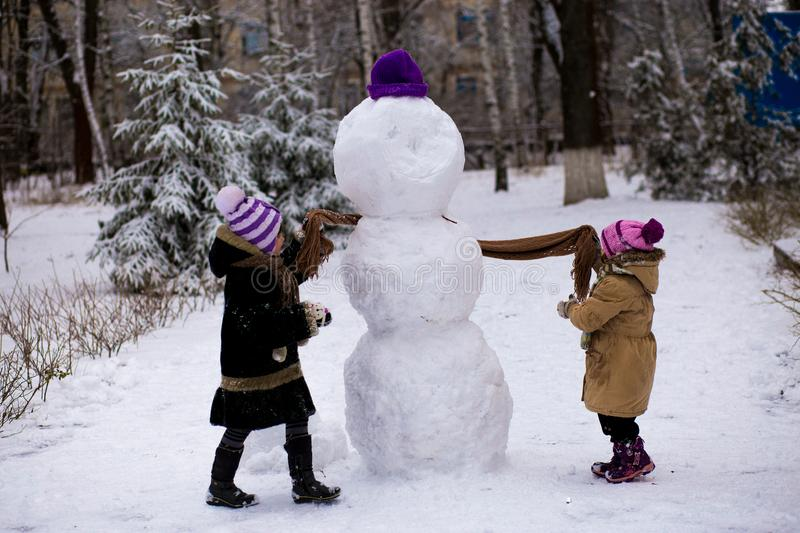 A small cheerful girls put on a scarf for a big snowman stock photo