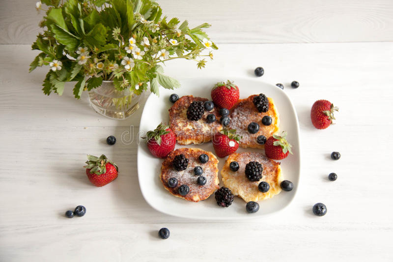 Small cheesecakes with fresh berries. Small homemade cheesecakes with fresh berries: strawberries, blackberries and blueberries with summer flower and leaves stock image