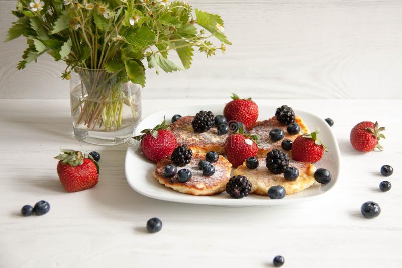 Small cheesecakes with fresh berries. Small homemade cheesecakes with fresh berries: strawberries, blackberries and blueberries with summer flower and leaves royalty free stock photo