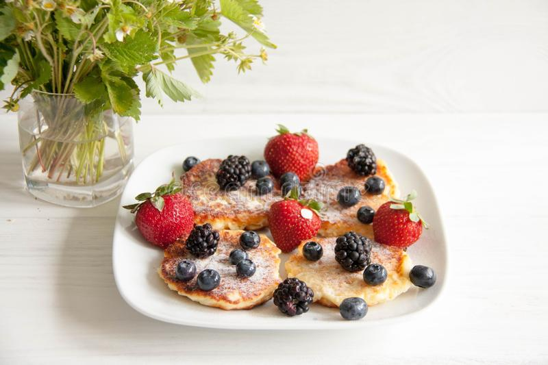 Small cheesecakes with fresh berries. Small homemade cheesecakes with fresh berries: strawberries, blackberries and blueberries with summer flower and leaves stock photos