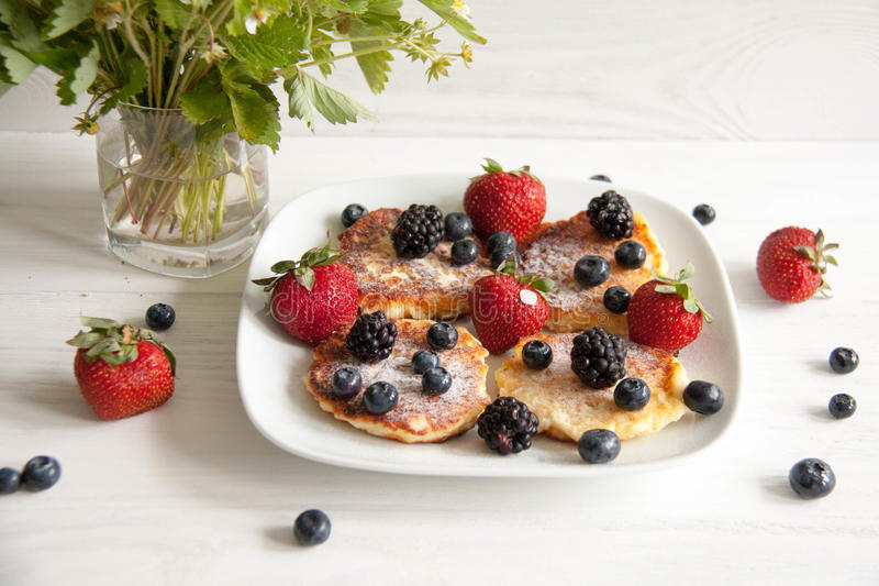 Small cheesecakes with fresh berries. Small homemade cheesecakes with fresh berries: strawberries, blackberries and blueberries with summer flower and leaves stock photography