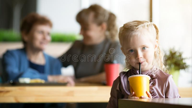 The girl drinks juice on the background of his mother and grandmother. A small child alone drinks a cocktail from the tub and the mother and grandmother are stock photography