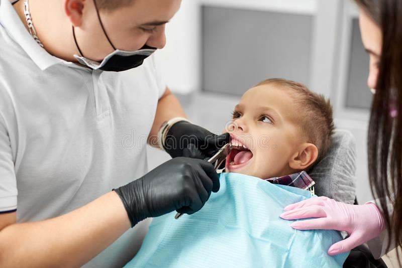 Child is calm and not scared having his teeth attended by a young male dentist in a white T-shirt and black gloves stock images