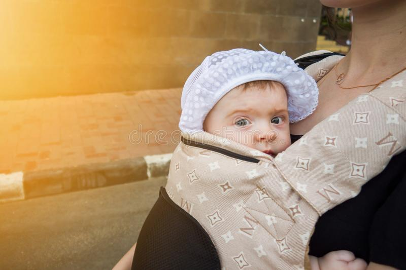 A small child in a children`s backpack with mom. Half a year old baby. Walk down the street. Summer day royalty free stock photos