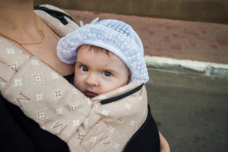 A small child in a children`s backpack with mom. Half a year old baby. Walk down the street. Summer day stock image