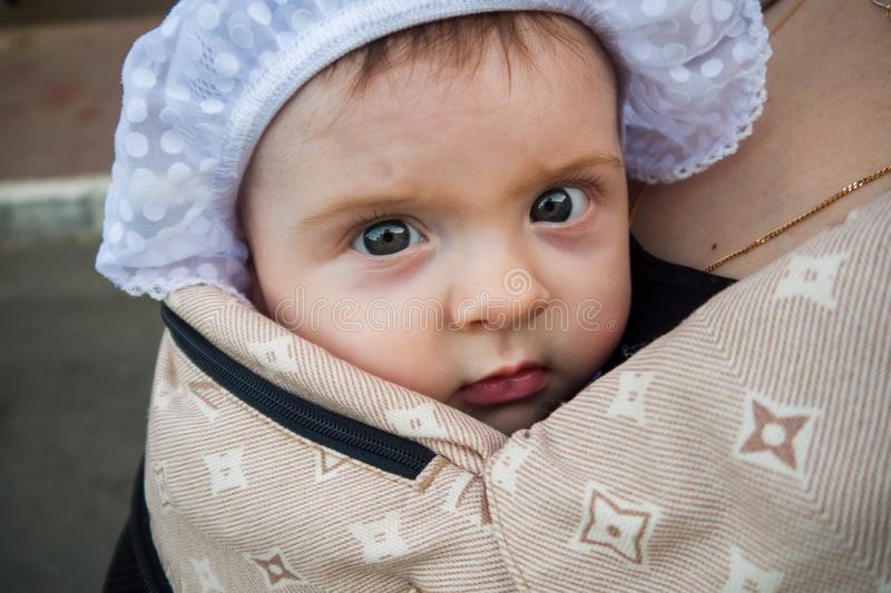 A small child in a children`s backpack with mom. Half a year old baby. Walk down the street. Summer day stock photos