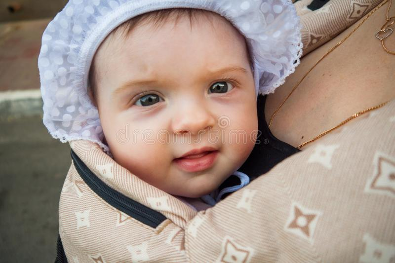 A small child in a children`s backpack with mom. Half a year old baby. Walk down the street. Summer day royalty free stock photo