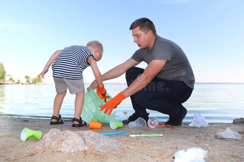 A small child collects trash on the beach. His dad points his finger where to throw garbage. Parents teach children cleanliness. stock image