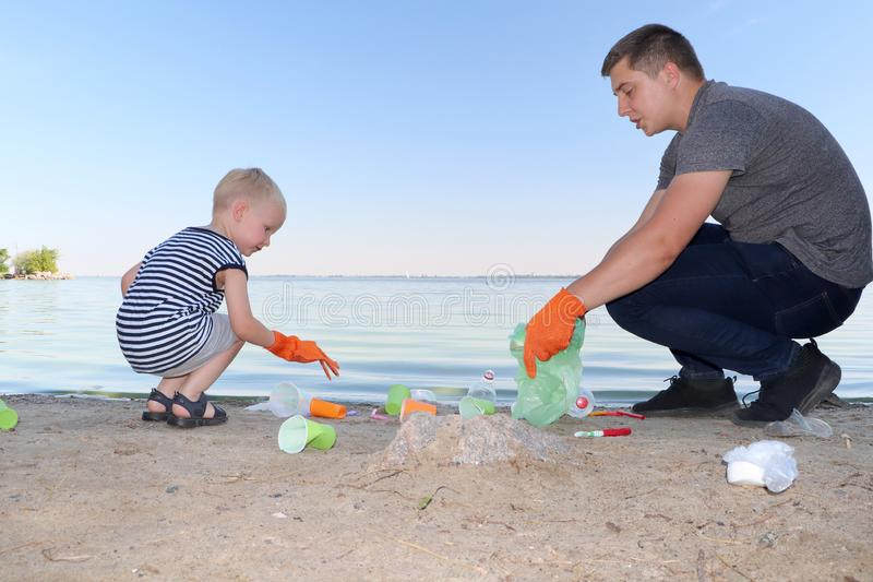 A small child collects trash on the beach. His dad points his finger where to throw garbage. Parents teach children cleanliness. royalty free stock photography