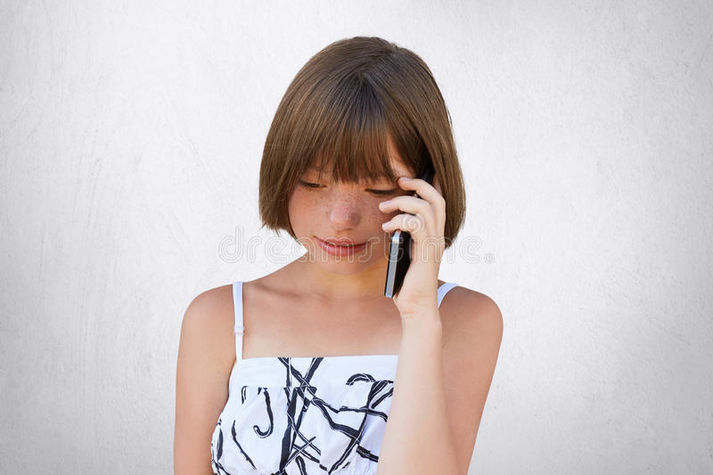 Small child communicating over smart phone with her parents while looking down. Pretty girl with short hair and frckles chatting o stock photos