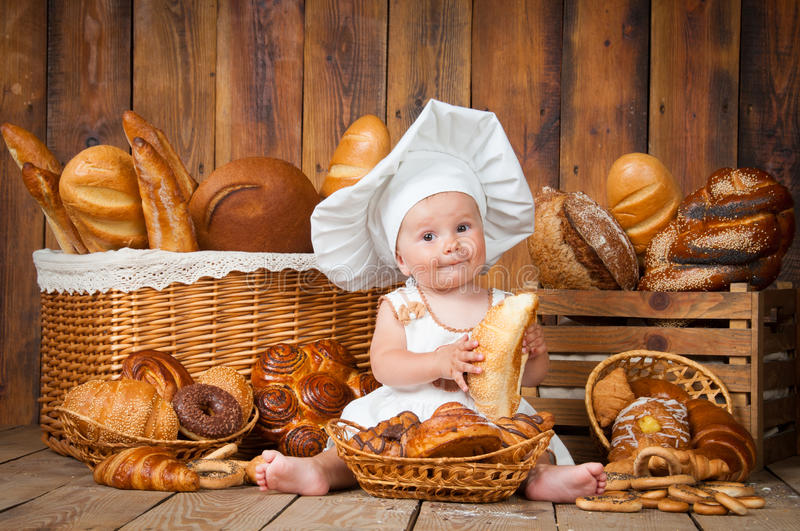 Small child cooks a croissant in the background of baskets with rolls and bread. royalty free stock photography