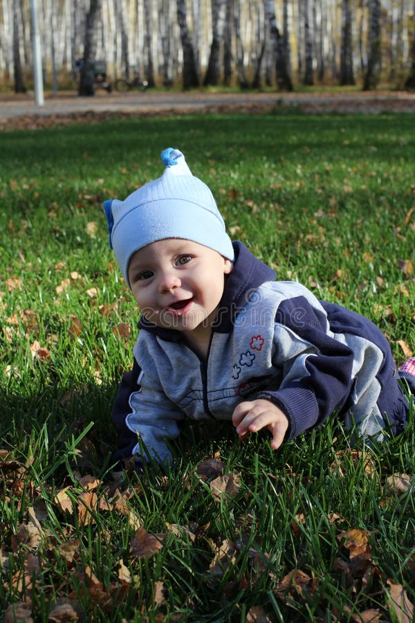 A small child crawling on the green grass on the lawn smiling royalty free stock image