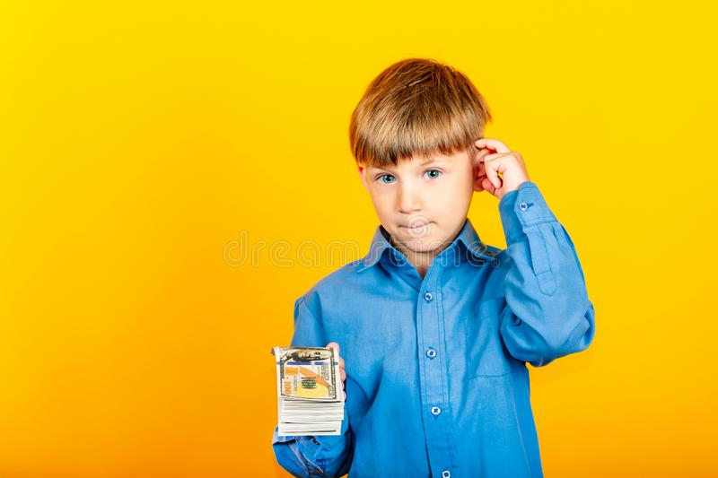 A small child with dollar bills, a boy holding a pack of dollar bills and offering it to you royalty free stock images