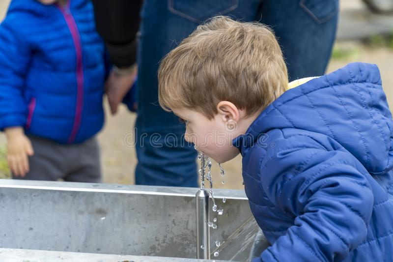 Small child drinking water in a park. Young boy drinking water from a outdoor tap spring stock photo