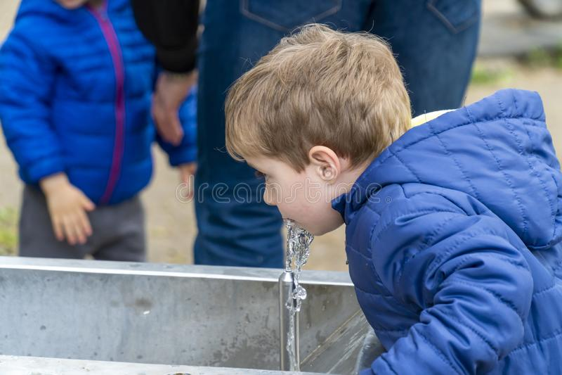 Small child drinking water in a park. Young boy drinking water from a outdoor tap spring stock image