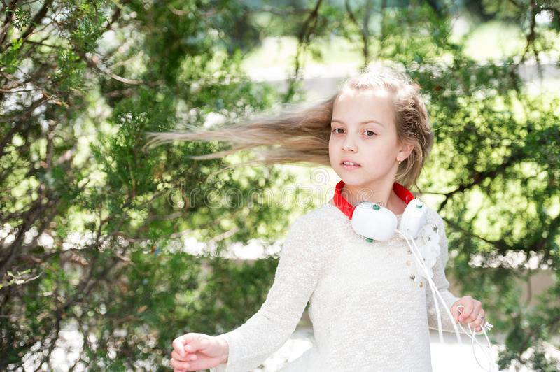 Small child enjoy music in headphones outdoor. Girl dance to music in summer park. Kid dancer with long flying hair. Melody sound and mp3. Summer fun and joy stock image