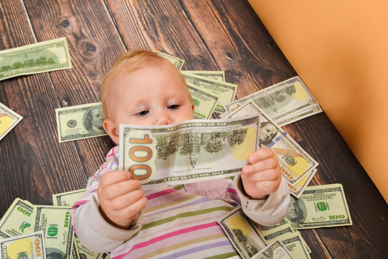 A small child examines a hundred-dollar crumpled bill, lying on the money. The concept of wealth and financial independence royalty free stock photography