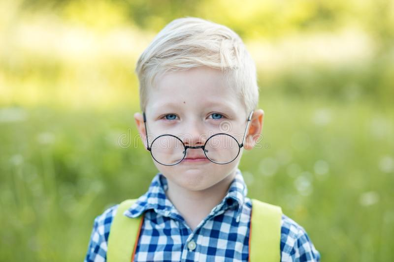 A small child with glasses and a backpack. Back to school. The concept of learning, school, mind, lifestyle stock image