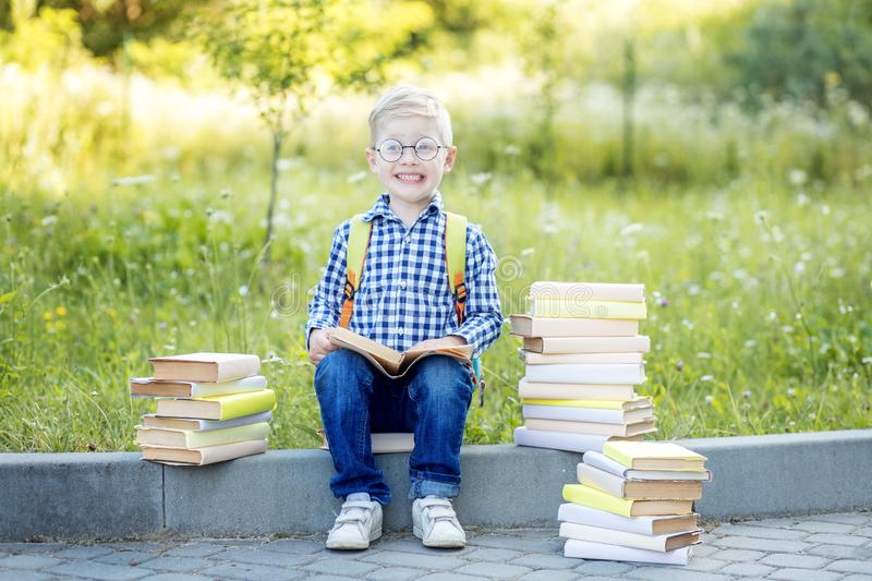 A small child with glasses and books. Back to school. The concept of learning, school, mind, lifestyle stock photography