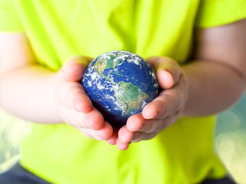 Small child in a green T-shirt holding the planet Earth in her hands. Earth day. Green concept royalty free stock image