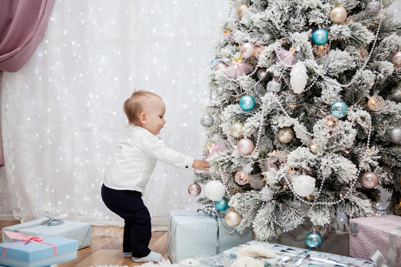 Small child hangs Christmas balls on the tree. A small child decorates a Christmas tree in a holiday beautiful interior royalty free stock photography
