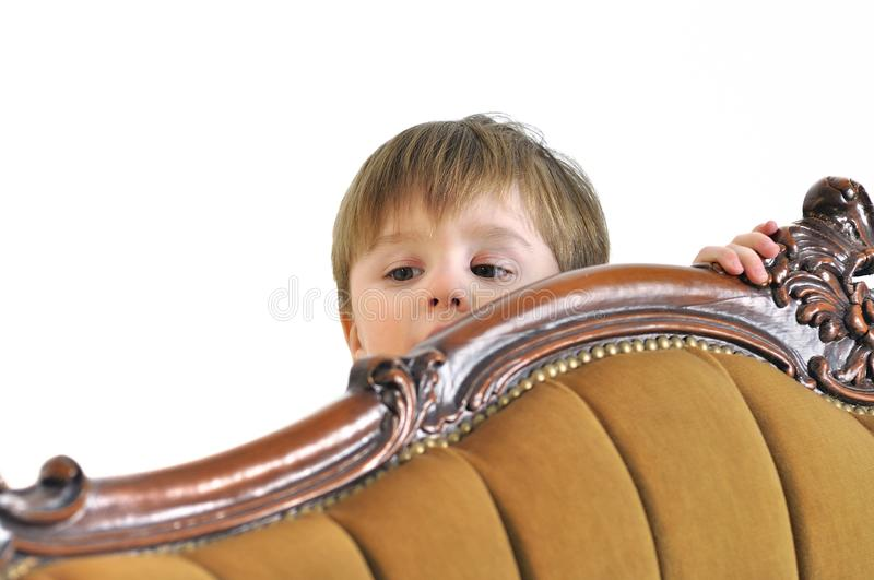 The small child hides behind a sofa and looks out. The small child hides behind sofa and looks out royalty free stock images