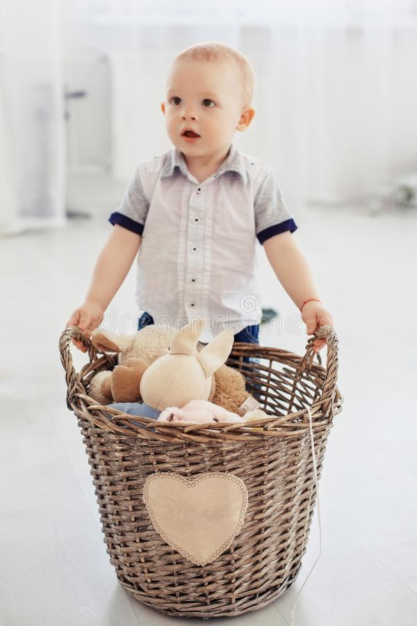 A small child holds a basket with toys. The concept of childhood stock images