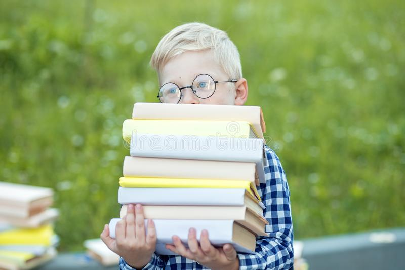 A small child holds many books in their hands. The concept of learning, school, mind, lifestyle and success royalty free stock photos