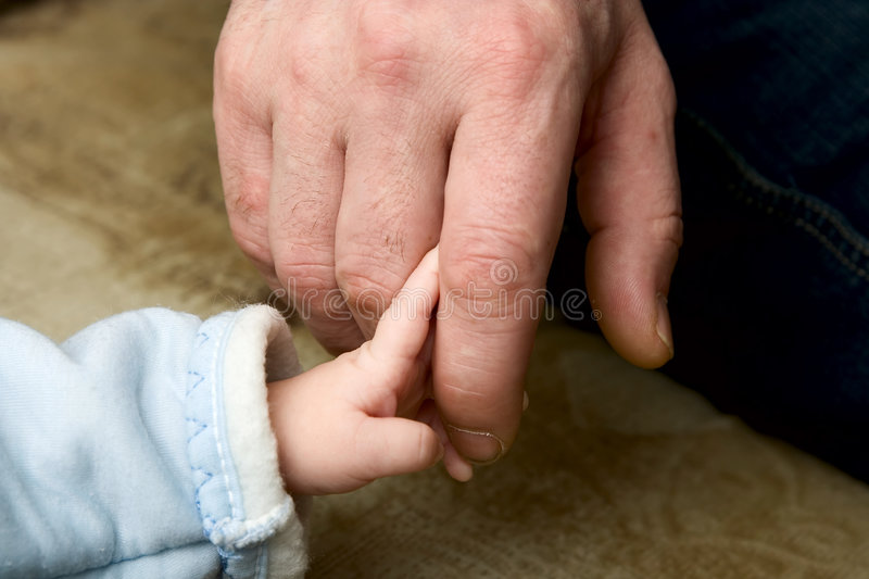 The small child keeping for a finger of the father royalty free stock photo