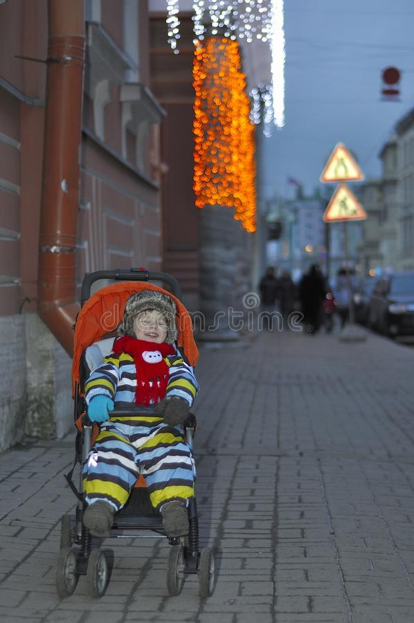 Small child laughs in a carriage in the evening stock images
