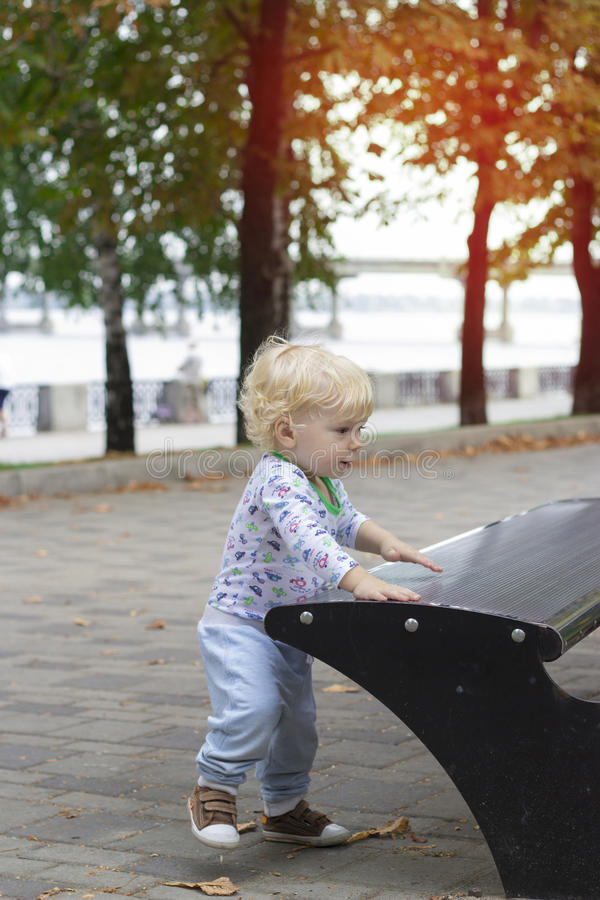 A small child learns to walk near the benches, toddler. A small child learns to walk near benches, toddler royalty free stock photos