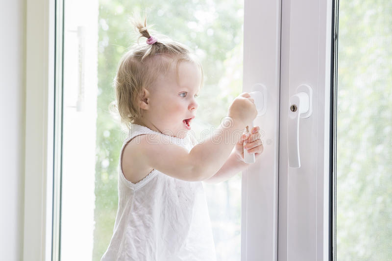 Small child opens window with key. girl is standing on window sill by window. stock images