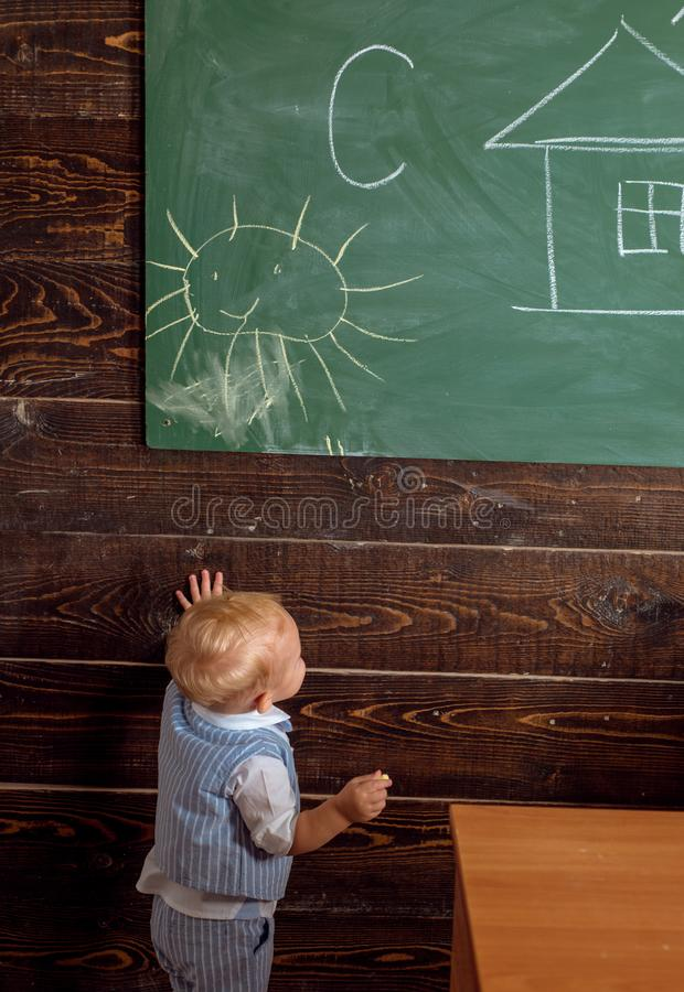 Small child painting picture on classroom chalkboard. Toddler in school of painting. Every artist was first an amateur royalty free stock photography