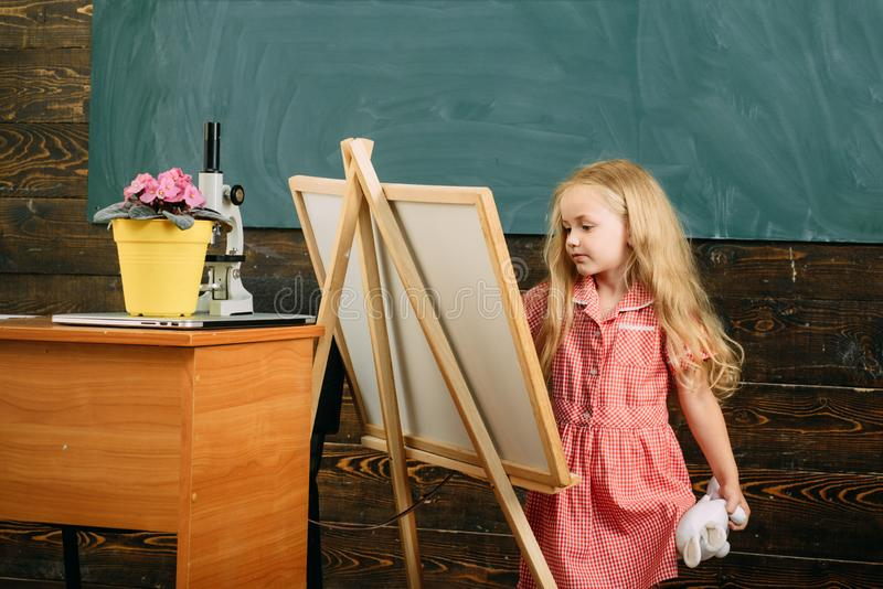 Small child painting picture on studio easel. Girl in painting studio stock photo
