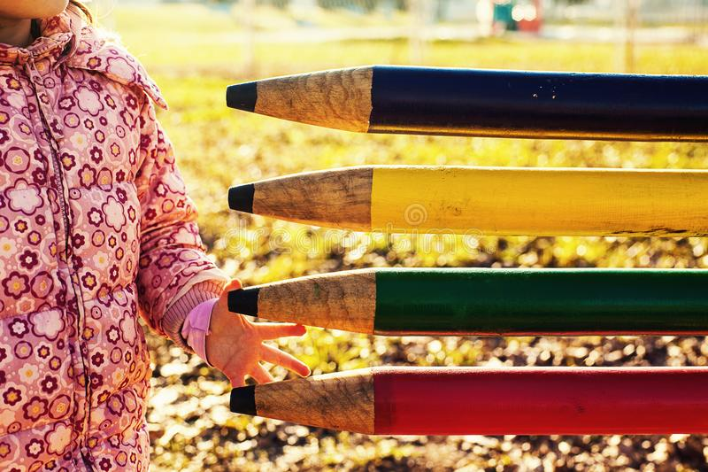 Big Colorful Wooden Pencils. Small child in park besides big wooden and colorful pencils stock photos
