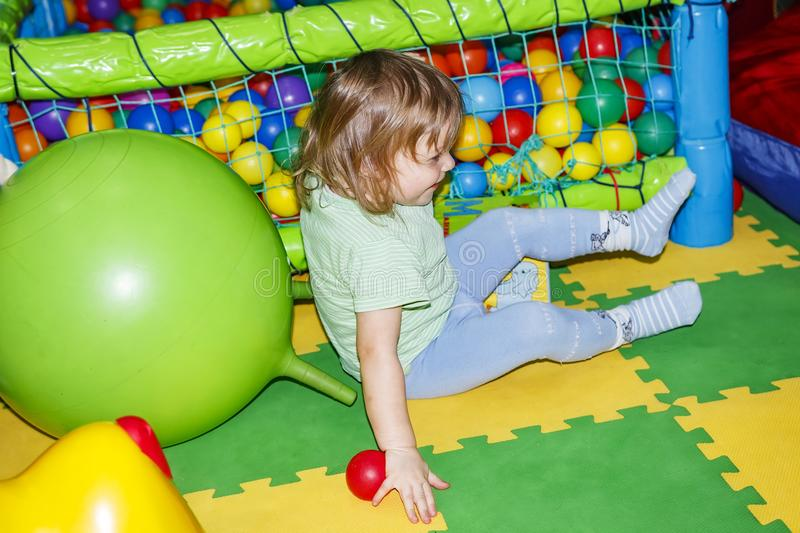 Small child is playing in children`s entertainment center stock image