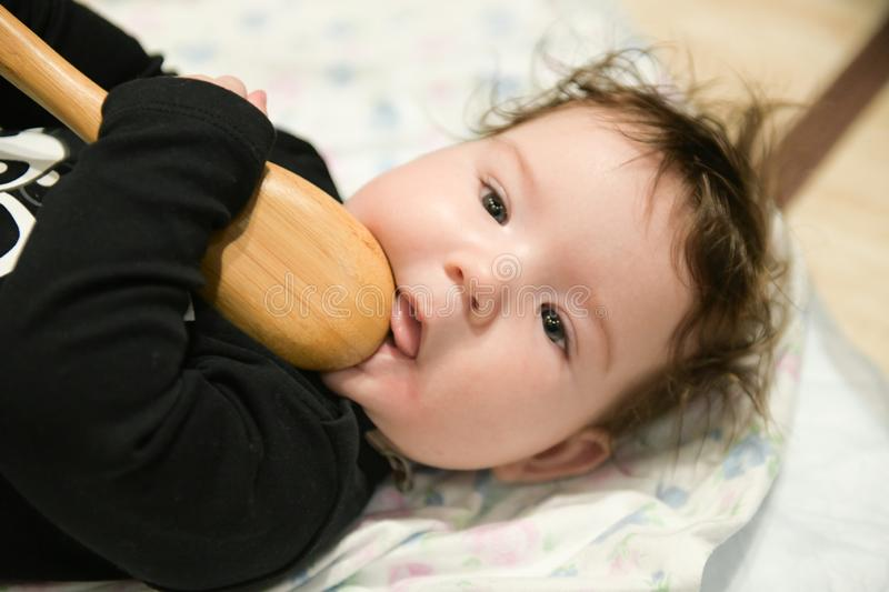 A small child is playing with a spoon. old kitchen toys. close up of babies hands playing with wooden spoon and pot baby chef royalty free stock photography