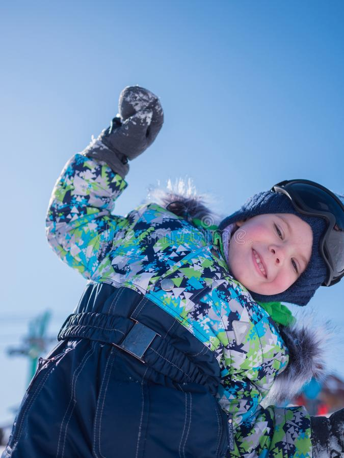 A small child playing in the winter Park. Playing and smiling baby on blue background . Active rest and games. royalty free stock images