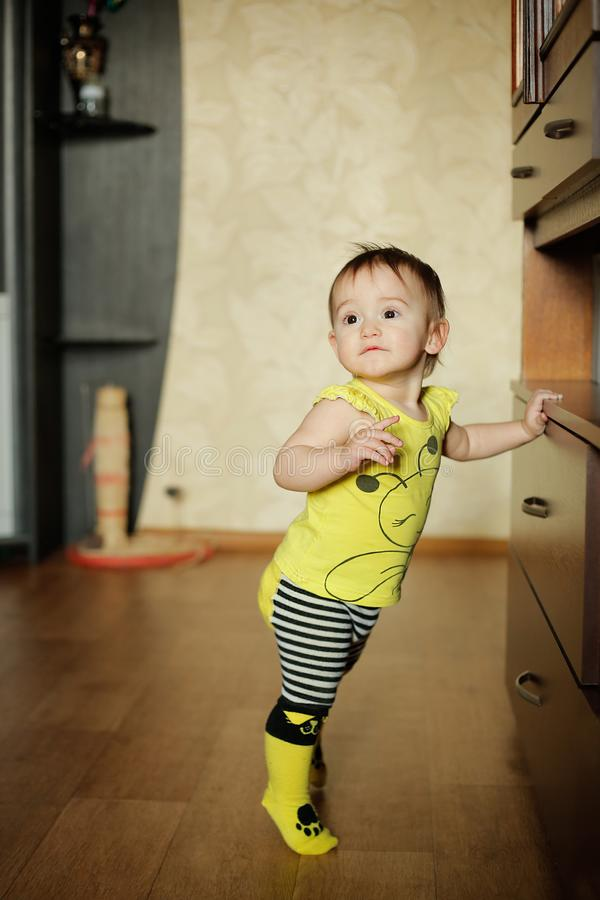 Little girl posing in clothes with a pattern of yellow bees stock images