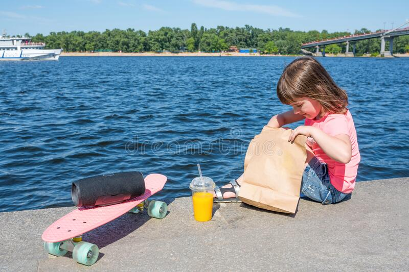 A small child on the promenade with a grocery bag.  Sunny summer day, fast food.  stock image