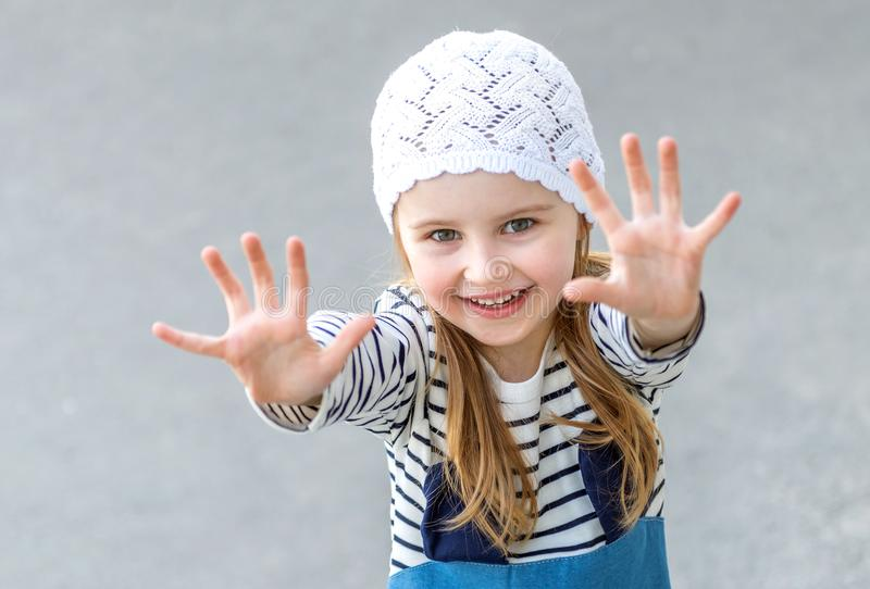 Small child reaching out with her hands. Smiling, wearing white cute har and jeans royalty free stock photos