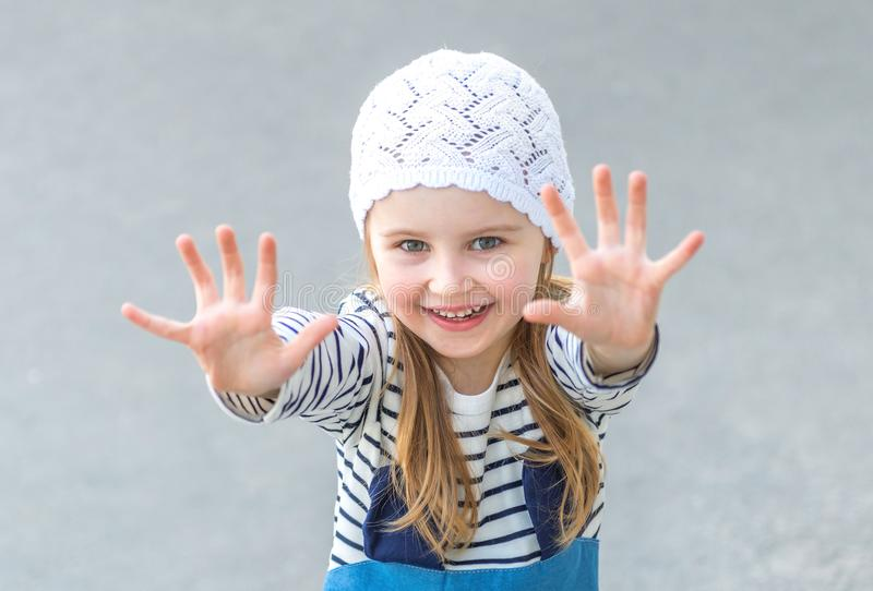 Small child reaching out with her hands. Smiling, wearing white cute har and jeans stock images