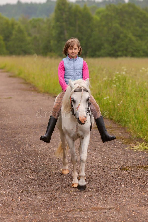 Free Small Child Riding On A White Horse On The Road Outdoors Royalty Free Stock Image - 57191236