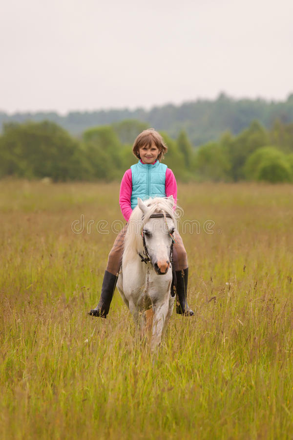 Small child riding on a white horse and smiling Outdoors royalty free stock photos