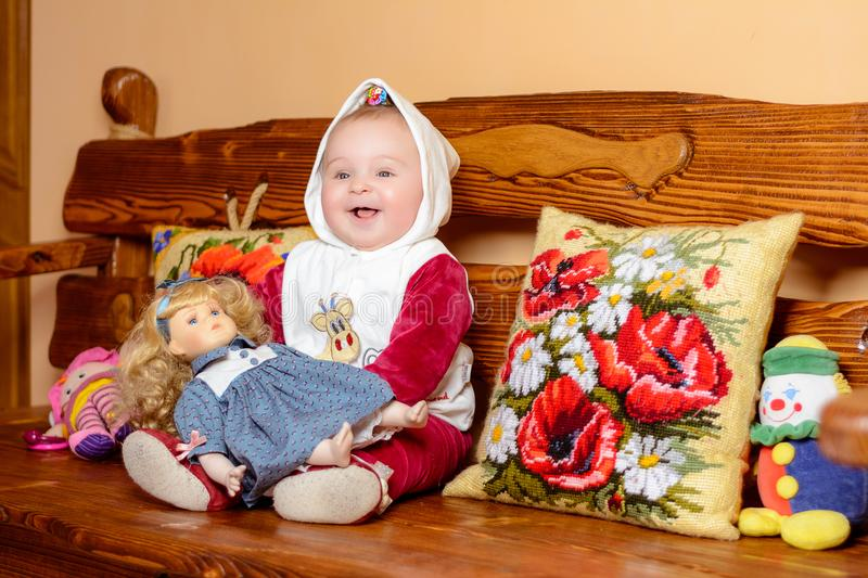 A small child in a shawl sitting on a sofa with embroidered pillows stock photos