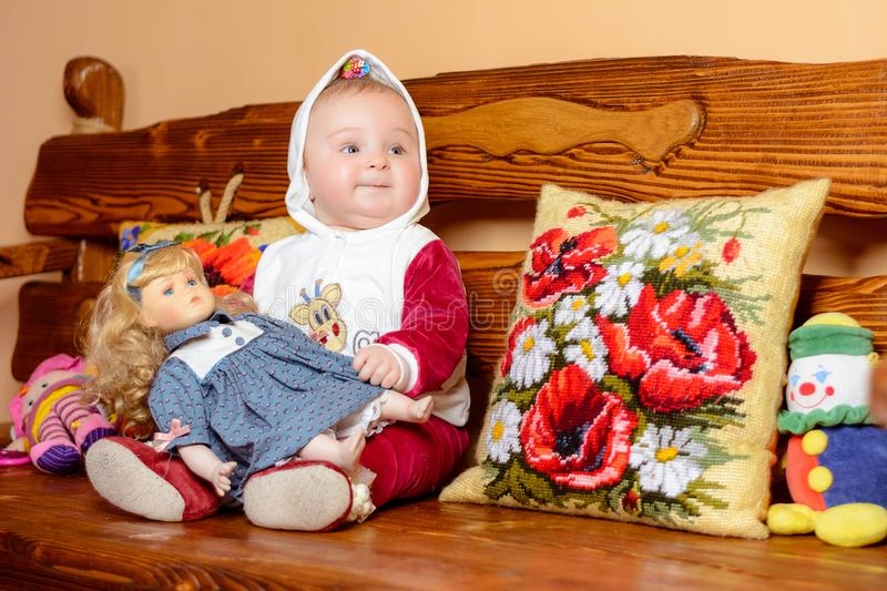 A small child in a shawl sitting on a sofa with embroidered pillows royalty free stock photography